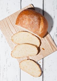 Frisch gebackenes brotlaib mit stücken auf hölzernem boardon weißem hölzernem brett