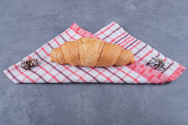 Frisch gebackenes croissant auf rosa baumwollserviette.