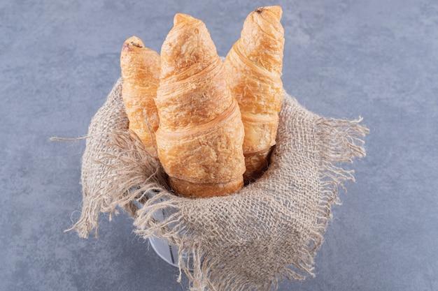 Frisch gebackenes croissant auf sack innerhalb des grauen eimers