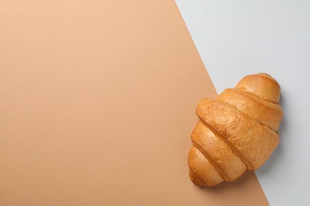 Frisch gebackenes croissant auf zweifarbigem hintergrund, draufsicht