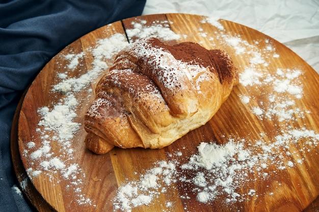 Frisch gebackenes croissant mit kondensmilch und schokoladenüberzug auf einem holzbrett. appetitliches französisches gebäck zum frühstück