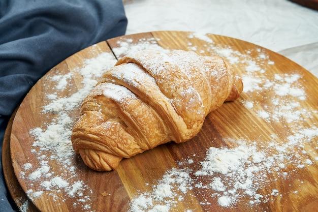 Frisch gebackenes croissant mit vanillesoße auf einem holzbrett. appetitliches französisches gebäck zum frühstück