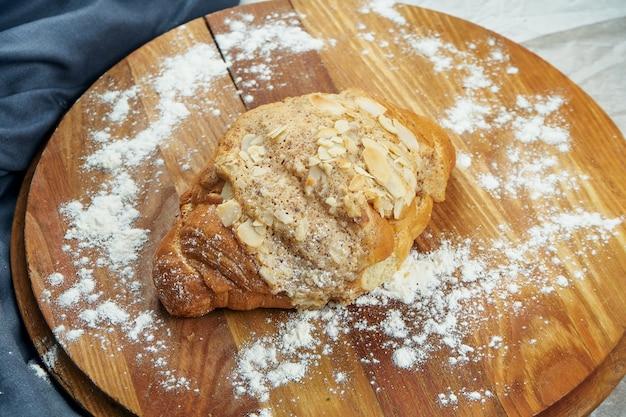 Frisch gebackenes croissant mit vanillesoße, mandeln auf einem holzbrett. appetitliches französisches gebäck zum frühstück