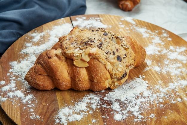 Frisch gebackenes croissant mit vanillesoße, mandeln und schokolade auf einem holzbrett. appetitliches französisches gebäck zum frühstück