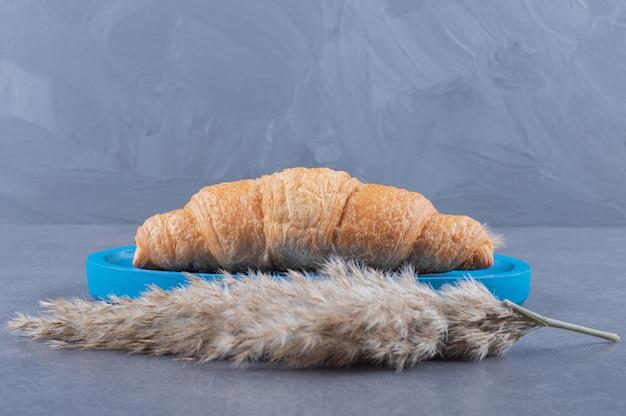 Frisch gebackenes französisches croissant auf blauem holzbrett.