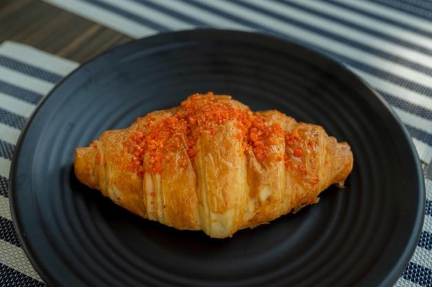 Frisch gebackenes gesalzenes eierpudding-lavacroissant auf schwarzem teller auf holztisch, französisches gebäck