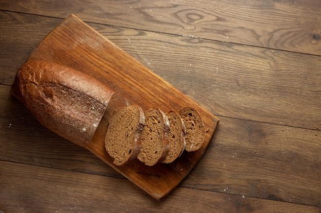 Frisch gebackenes geschnittenes roggenbrot auf einem hölzernen schneidebrett, flache lage, kopienraum