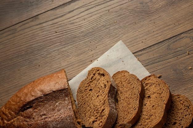 Frisch gebackenes geschnittenes roggenbrot auf einem hölzernen schneidebrett