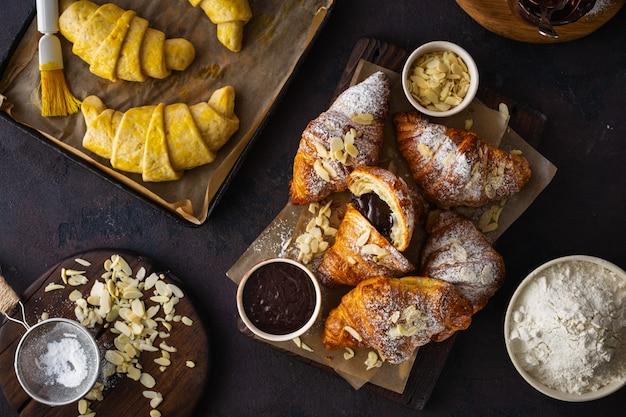 Frisch gebackenes hörnchen mit draufsicht der mandelflocken und des puderzuckers