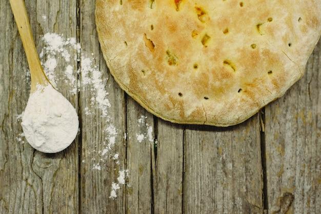 Frisch gebackenes pizza calzone auf gealtertem hölzernem brett mit dem löffel voll vom mehl