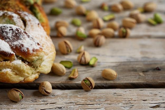 Frisch gebackenes süßes brötchen des zimts mit pistaziencreme und -pistazie auf rustikalem holztisch