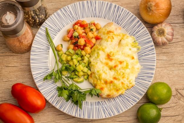 Frisch gebackenes tilapiafischabendessen mit frischen kräutern und in der knoblauchsoße.