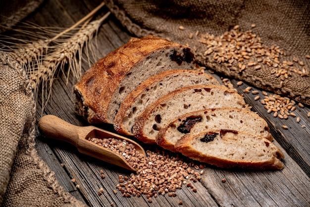 Frisch gebackenes traditionelles brot auf holztisch. rustikales brot mit buchweizen und pflaumen