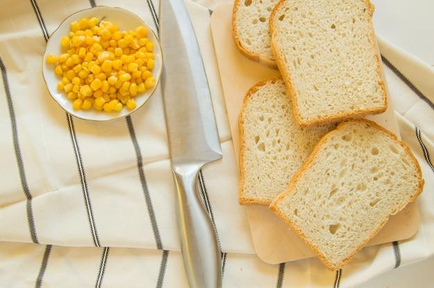 Frisch gebackenes traditionelles weizenbrot, maiskörner und messer auf leinengeschirrtuch, flache lage