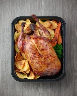 Frisch gebratene ente und gemüse in kunststoffbehälter zur lieferung auf grauem küchentisch aus holz, ansicht von oben