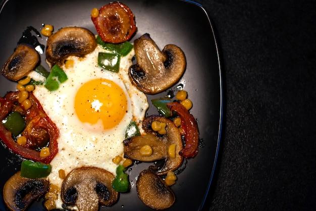 Frisch gebratenes rührei mit gemüse auf einer schwarzen platte