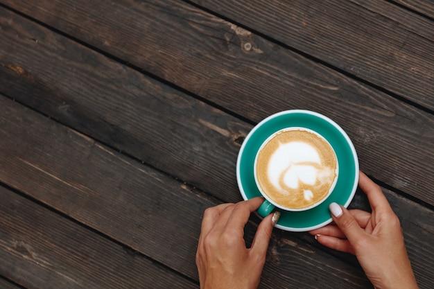 Frisch gebrühter heißer kaffee mit schöner latte art in herzform in türkisfarbenem tassenhalter von einer frau in händen