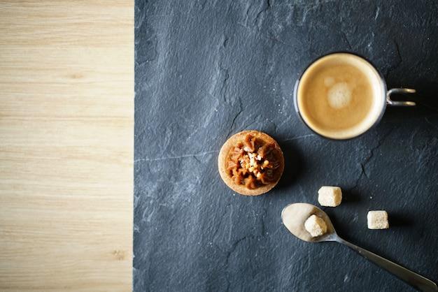 Frisch gebrühter kaffee auf schiefer mit zuckerminigebäck mit textraum