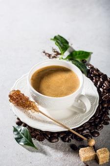 Frisch gebrühter kaffee in einer weißen tasse mit bohnen und blättern. lebensmitteloberfläche mit kopierraum