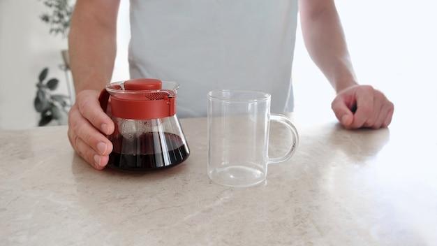 Frisch gebrühter kaffee in glasserver und glasschale auf tisch. pourover, v60.