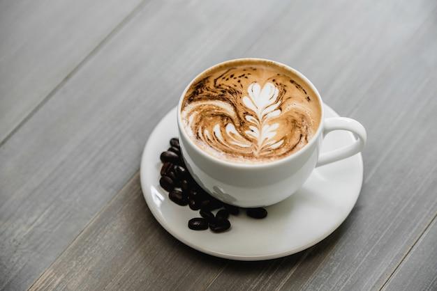 Frisch gebrühter kaffee mit latte-kunst des farnmusters in der weißen tasse