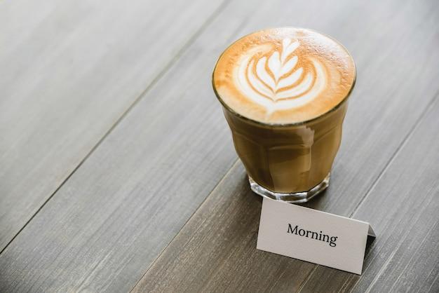 Frisch gebrühter kaffee mit schöner lattekunst auf holztisch