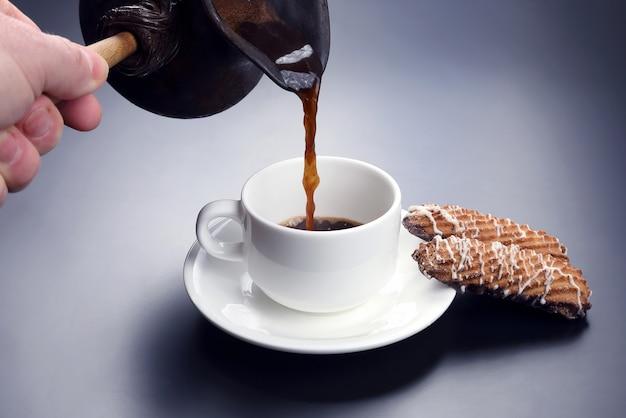Frisch gebrühter schwarzer kaffee von den türken in eine weiße tasse gegossen