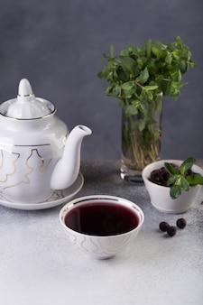 Frisch gebrühter tee wird in eine schüssel gegossen, daneben ein schokoladenkuchen, der mit einem zweig frischer kräuter dekoriert ist