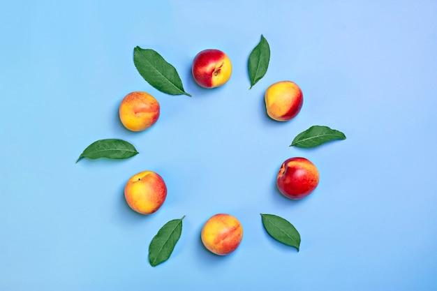 Frisch geerntete nektarinen liegt auf blauem hintergrund pflanzliches vitamin keratin natural