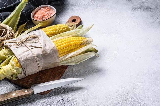 Frisch geernteter maiskolben auf bauernmarkt, lokales gemüse. grauer hintergrund. draufsicht.