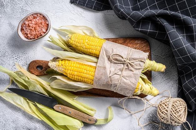 Frisch geernteter maiskolben auf bauernmarkt, lokales gemüse. grauer hintergrund.