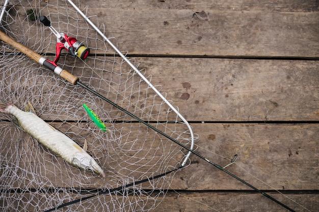Frisch gefangener fisch innerhalb des fischernetzes mit angelrute