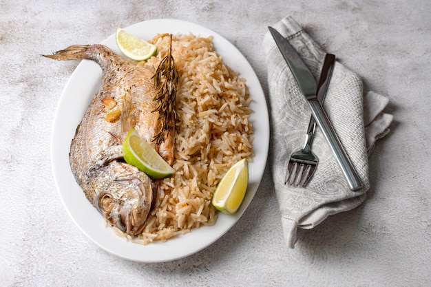 Frisch gegrillter dorado- oder seebrassenfisch mit zitrone und rosmarin, serviert mit reis. köstlicher dorada-fisch, der auf grill im fischrestaurant gekocht wird. gesundes essen. draufsicht, freier kopierplatz.