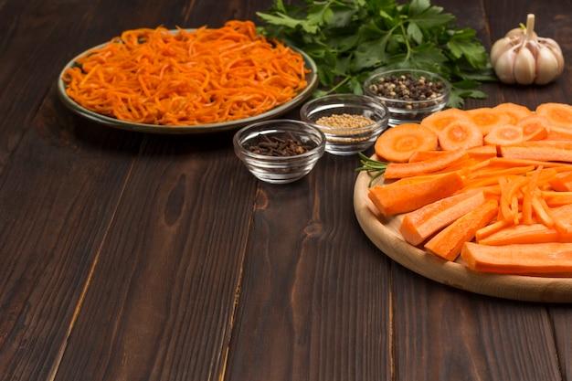 Frisch gehackte karotten auf schneidebrett. fermentierte karotten in platte. gewürze, knoblauch und petersilie auf dem tisch. natürliches heilmittel zur stärkung des immunsystems. nahansicht. speicherplatz kopieren