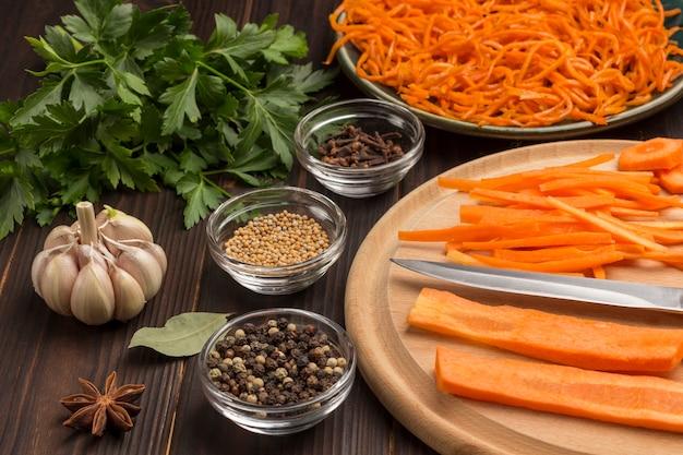 Frisch gehackte karotten auf schneidebrett. fermentierte karotten in platte. gewürze, knoblauch und petersilie auf dem tisch. natürliches heilmittel zur stärkung des immunsystems. nahansicht