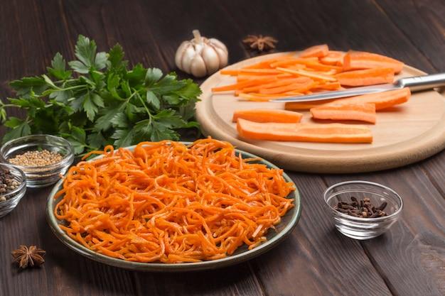 Frisch gehackte karotten auf schneidebrett. fermentierte karotten in platte. gewürze, knoblauch und petersilie auf dem tisch. natürliches heilmittel zur stärkung des immunsystems