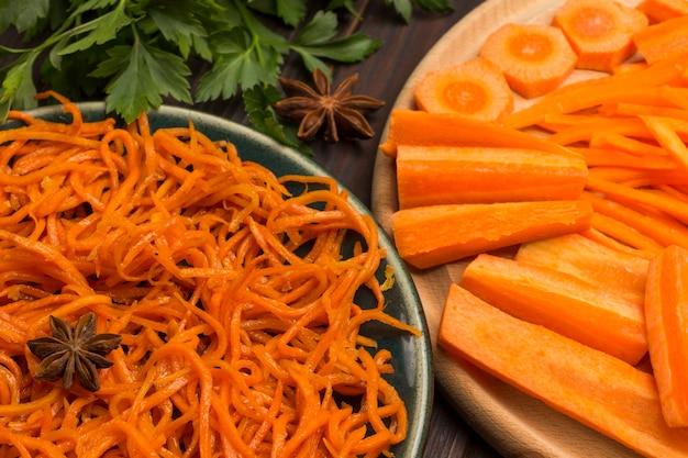 Frisch gehackte karotten auf schneidebrett. fermentierte karotten in platte. natürliches heilmittel zur stärkung des immunsystems. nahansicht