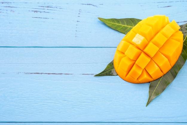 Frisch gehackte mango mit grünen blättern auf hellblauem holzhintergrund