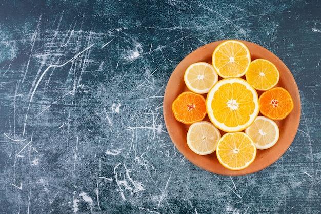 Frisch gehackte zitrusfrüchte in eine runde tonplatte gelegt.