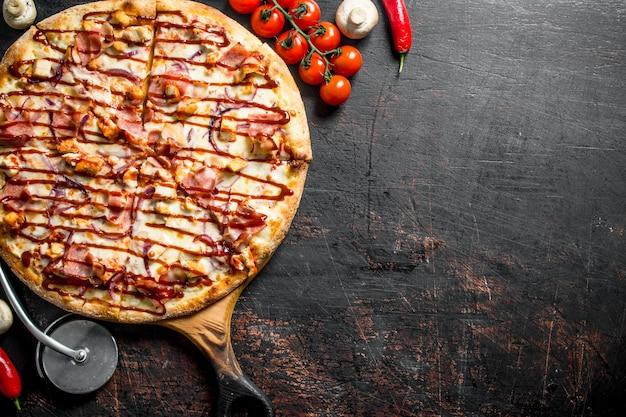 Frisch gekochte grillpizza auf einem schneidebrett. auf dunklem rustikalem hintergrund