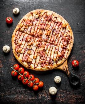 Frisch gekochte grillpizza auf einem schneidebrett. auf dunkler rustikaler oberfläche