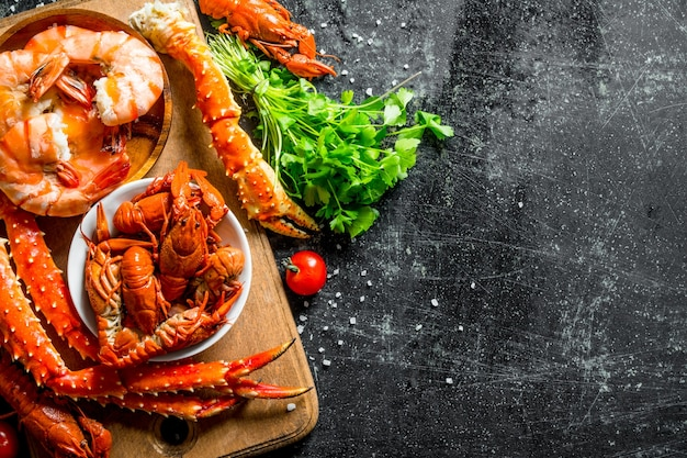 Frisch gekochte krebse, krabben und garnelen mit kräutern. auf dunklem rustikalem hintergrund