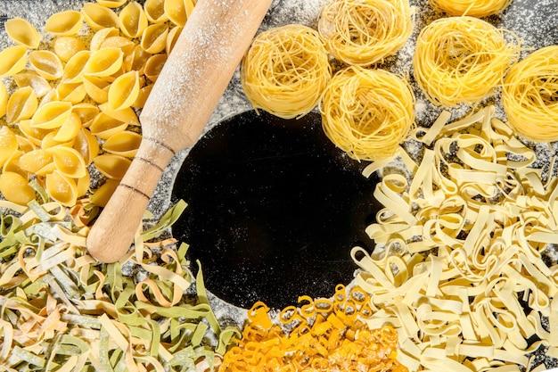 Frisch gekochte nudeln liegen auf einer dunklen, mit mehl bestäubten oberfläche. italienische pasta. tagliatelle. rohe nudeln. italienisches pasta-rezept. ansicht von oben, kopienraum.