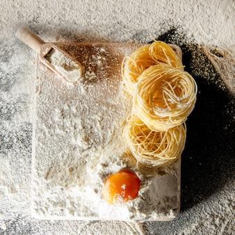 Frisch gekochte nudeln liegen auf einer dunklen oberfläche, die mit mehl bestäubt ist. italienische pasta