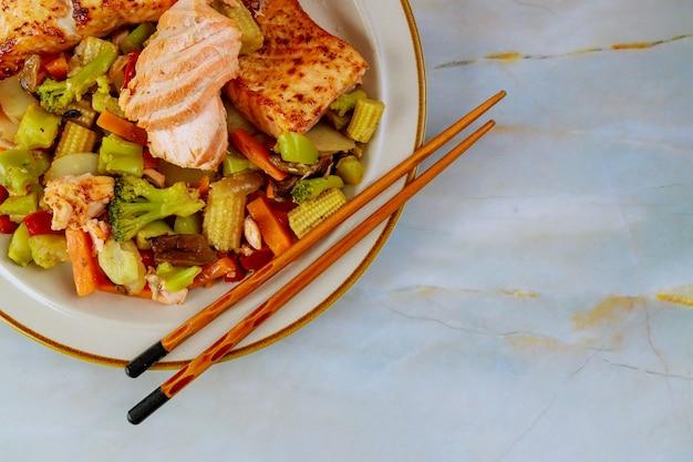 Frisch gekochter lachs in teller mit salat und zitrone auf weißem tisch.