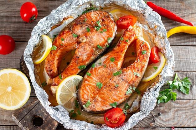 Frisch gekochtes köstliches lachssteak mit gewürzen und kräutern, die auf einem grill auf einem holztisch gebacken werden. gesundes meeresfrüchte-essen. ansicht von oben