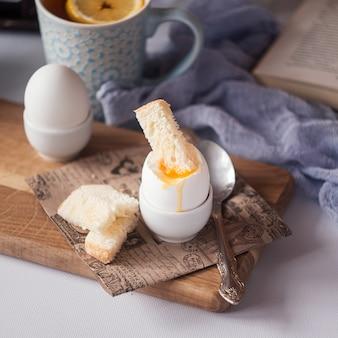 Frisch gekochtes weißes ei auf hölzernem brett. gesundes fitness-frühstück