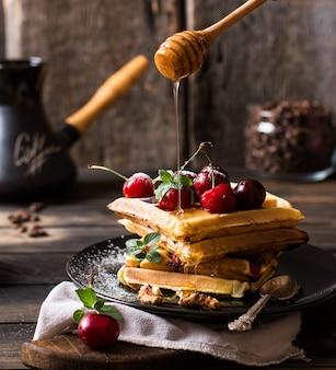 Frisch gemachte belgische waffeln mit honigstrom und puderzucker. kirschen auf waffeln auf hölzernem schreibtisch und serviette auf hölzernem hintergrund. kaffeebohnen im glas. türkisches kaffeetopf zum frühstück