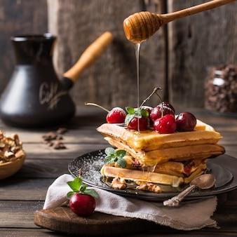 Frisch gemachte belgische waffeln mit honigstrom und puderzucker.