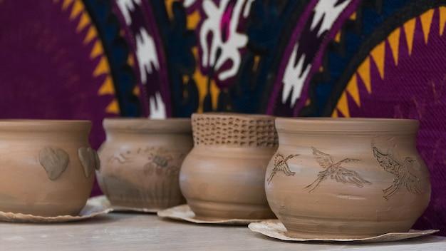 Frisch gemachte tontöpfe auf einem dekorativen hintergrund. kinderhandwerk